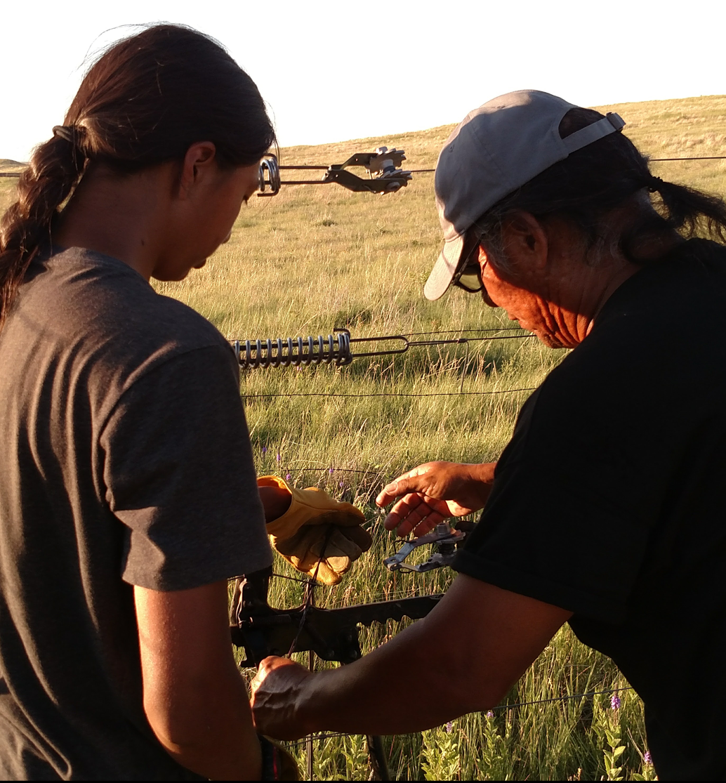 Two family members from the Knife Chief Buffalo Nation Society work on fixing a fence.