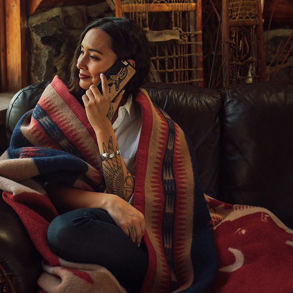 A young woman sits wrapped in the Tanka Blanket.