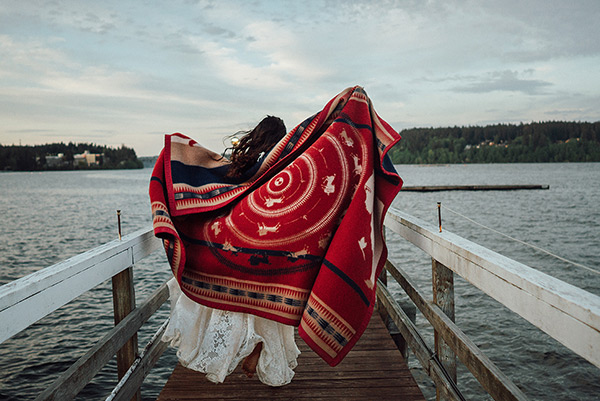 A woman standing near water and holding out the Tanka Blanket behind her.
